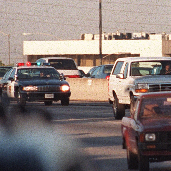 Motorists wave as police cars pursue the Ford Bronco driven by Al Cowlings, carrying O.J. Simpson, on a 90-minute slow-speed car chase June 17, 1994 on the 405 freeway in Los Angeles. (Credit: MIKE NELSON/AFP/Getty Images)