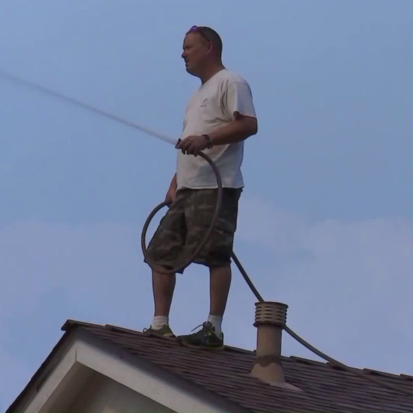 A resident of McGroarty Terrace in Tujunga sprays down his and his neighbors' homes in attempt to protect them from fire damage. (Credit: KTLA)