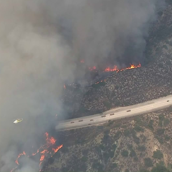 A helicopter crosses in front of a huge plume of smoke from a wildfire in Tujunga on Sept. 1, 2017. (Credit: KTLA)