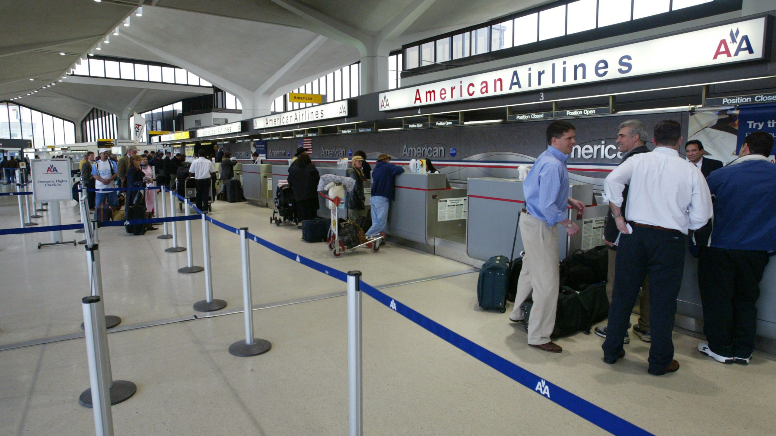 Passengers wait at a ticket counter at Newark Liberty International Airport on April 3, 2003. (Credit: Matthew Peyton/Getty Images)