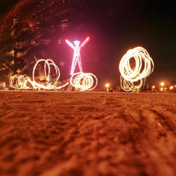 """Dancers at the """"Burning Man"""" festival create patterns with fireworks in the Black Rock Desert of Nevada just prior to burning a five-story, neon-lit effigy of a man on the last night of the week-long festival on Sept. 6, 1998. (Credit: Mike Nelson / AFP / Getty Images)"""