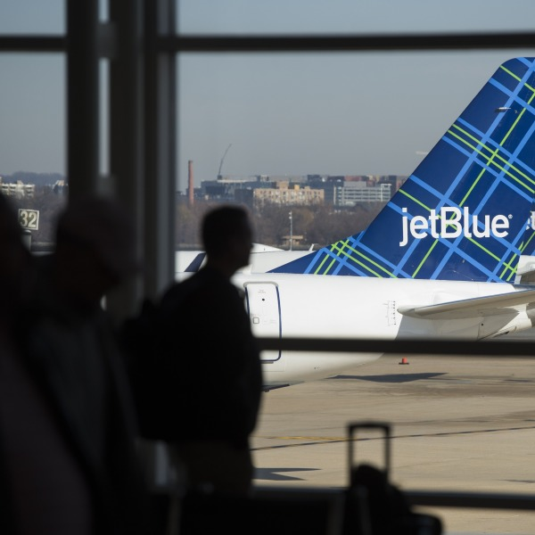 Travelers walk past the tails of JetBlue airplanes in the airport terminal at Ronald Reagan Washington National Airport in Arlington, Virginia, on Dec. 22, 2016. (Credit: Saul Loeb / AFP / Getty Images)