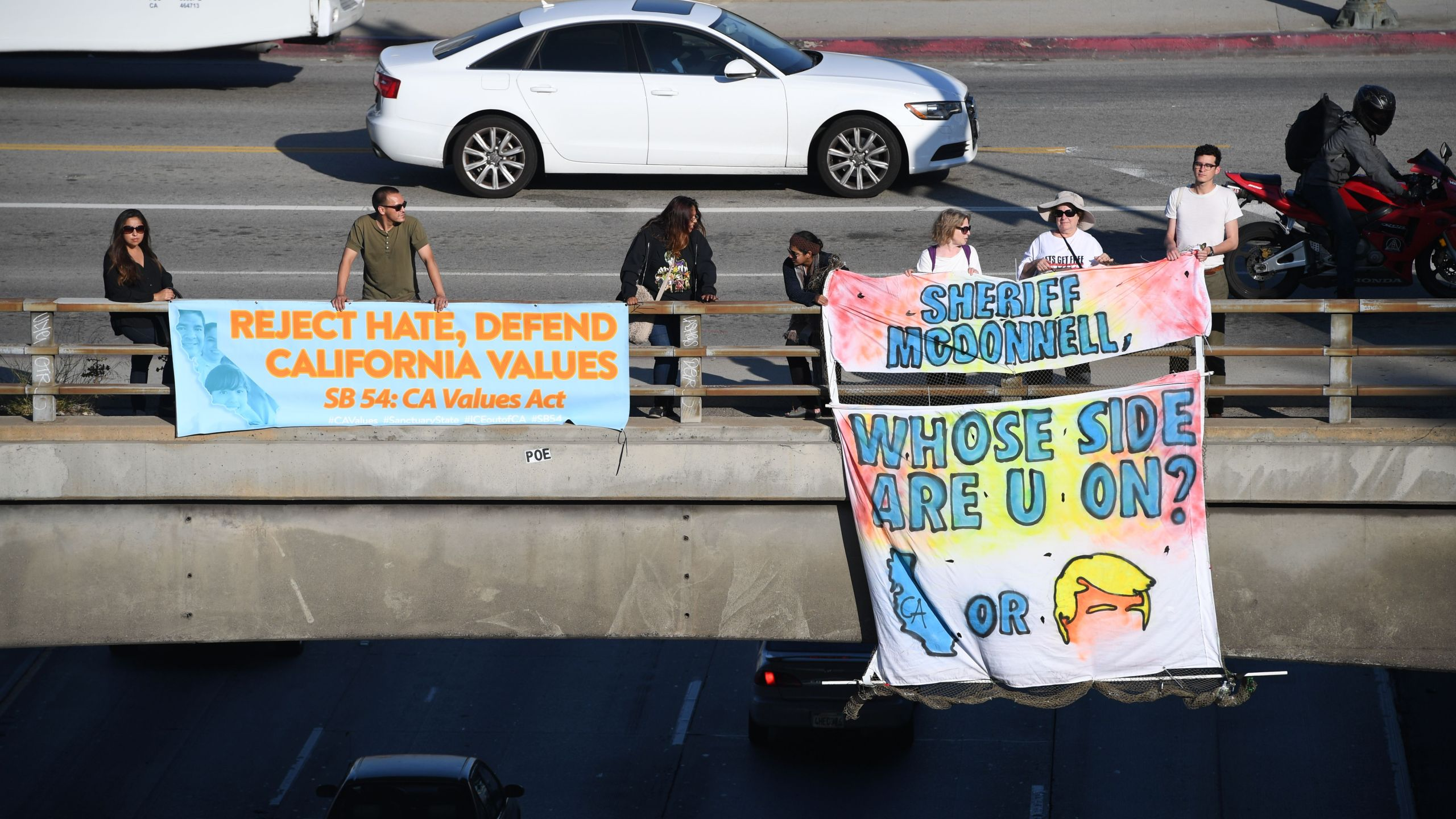 Protesters hold banners critical of Los Angeles County Sheriff Jim McDonnell's position against Senate Bill 54, the California Sanctuary State Bill or California Values Act, on a freeway overpass in downtown Los Angeles on May 24, 2017. (Credit: Robyn Beck / AFP / Getty Images)