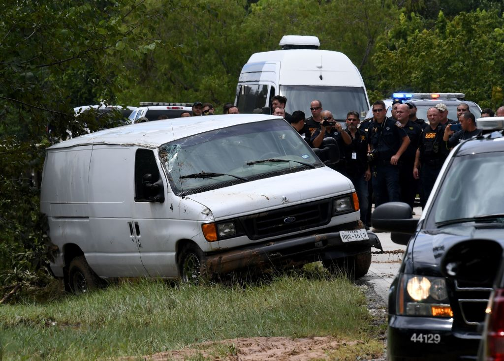Police investigators watch as the van containing the six members of the the Saldivar family who died is towed to the road after they crashed their van into Greens Bayou as they tried to flee Hurricane Harvey during heavy flooding in Houston, Texas on August 30, 2017. / AFP PHOTO / MARK RALSTON (Photo credit should read MARK RALSTON/AFP/Getty Images)