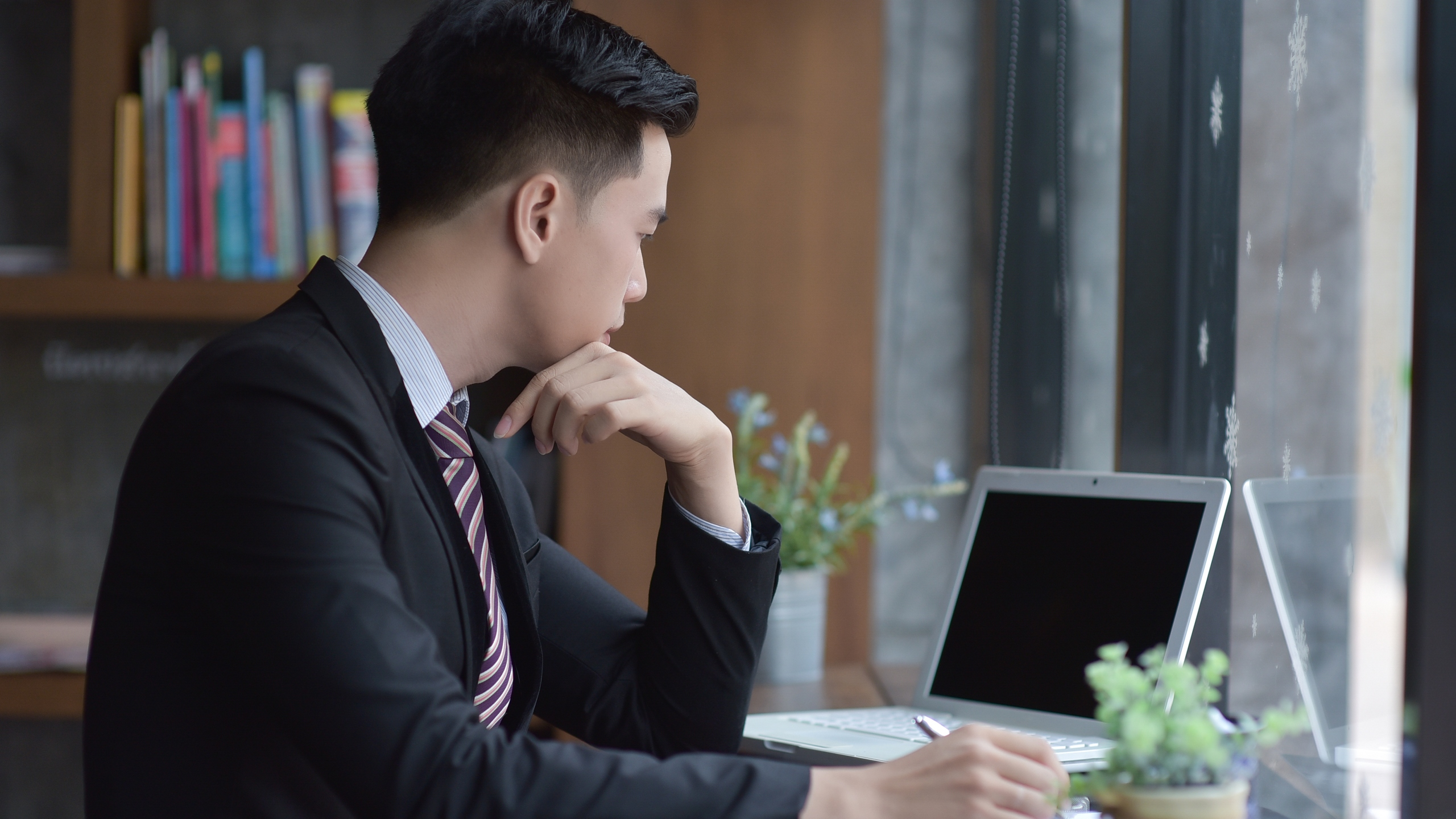 A young business man is seen sitting at his desk in this file photo. (Credit: iStock / Getty Images Plus)