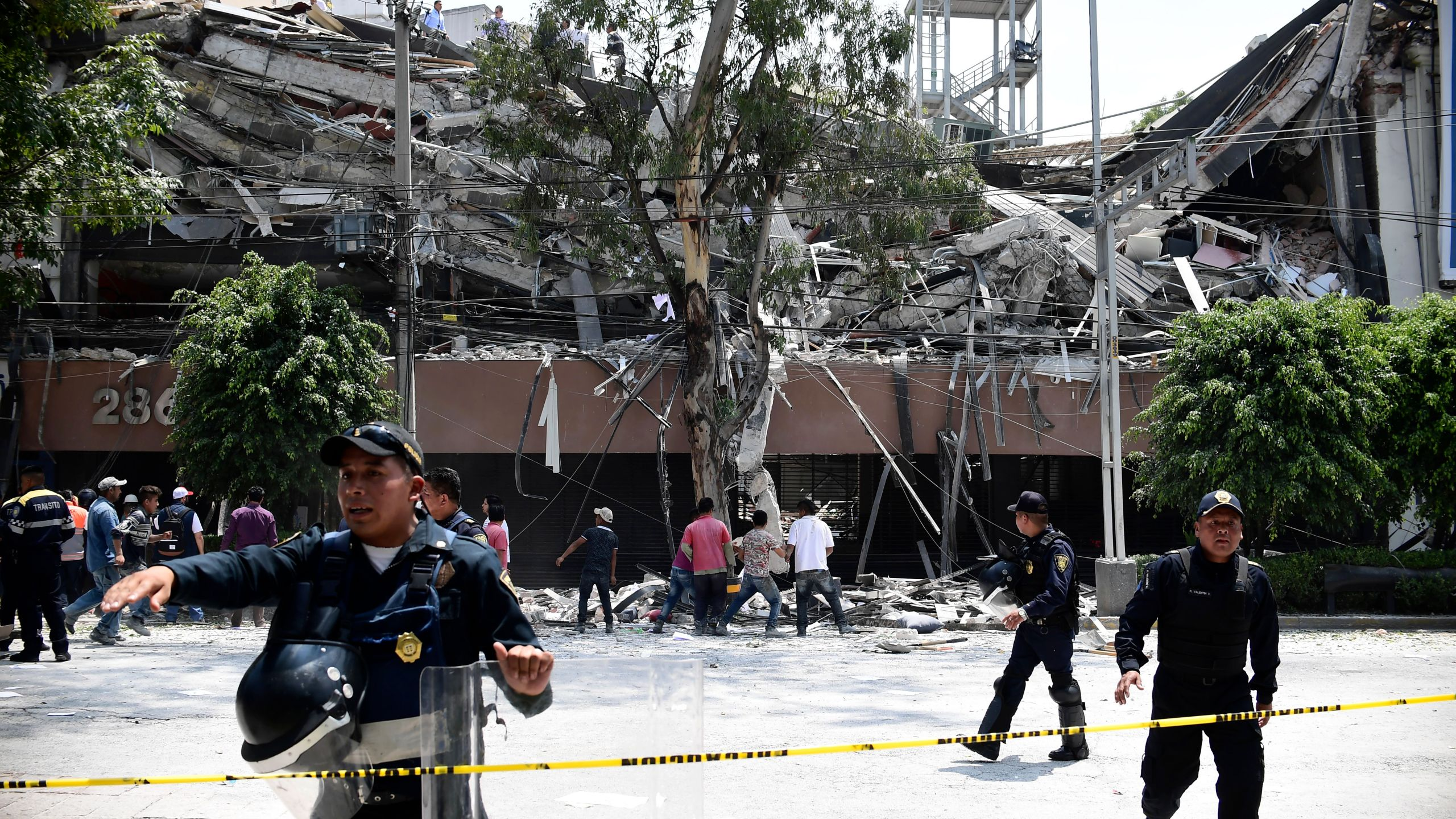 Police officers cordon the area off after a building collapsed during a quake in Mexico City on Sept. 19, 2017. (Credit: RONALDO SCHEMIDT/AFP/Getty Images)