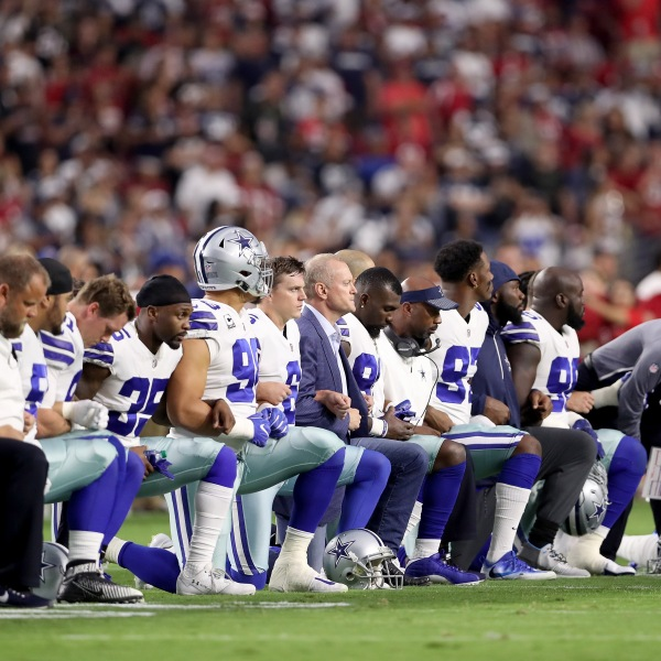 Members of the Dallas Cowboys link arms and kneel during the National Anthem before the start of the NFL game against the Arizona Cardinals at the University of Phoenix Stadium on September 25, 2017 (Credit: Christian Petersen/Getty Images)