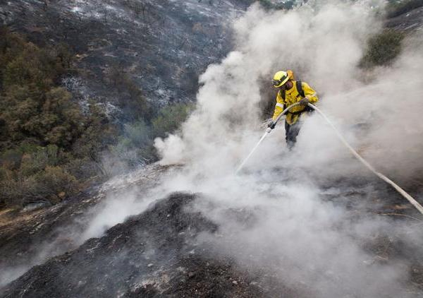 L.A. County firefighter Kevin Sleight extinguishes hot spots while battling the La Tuna fire along Crestline Drive in Los Angeles on Sept. 3, 2017. (Credit: Allen J. Schaben / Los Angeles Times)