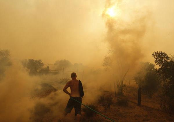 Sunland resident Jeff Dalton sprays water near his home as flames from the La Tuna fire approach. (Credit: Genaro Molina / Los Angeles Times)