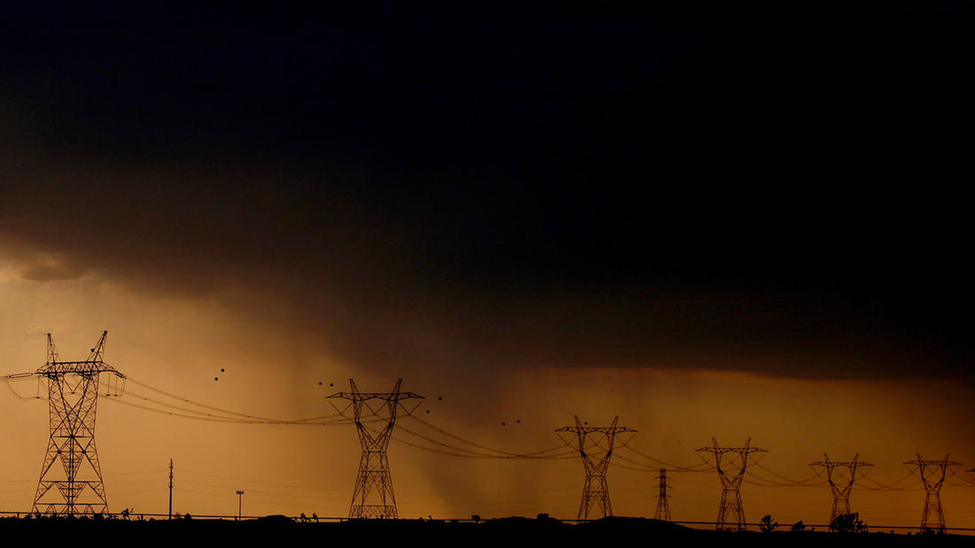 Rain falls behind power lines near Adelanto at the end of a scorching hot day. (Credit: Luis Sinco / Los Angeles Times)