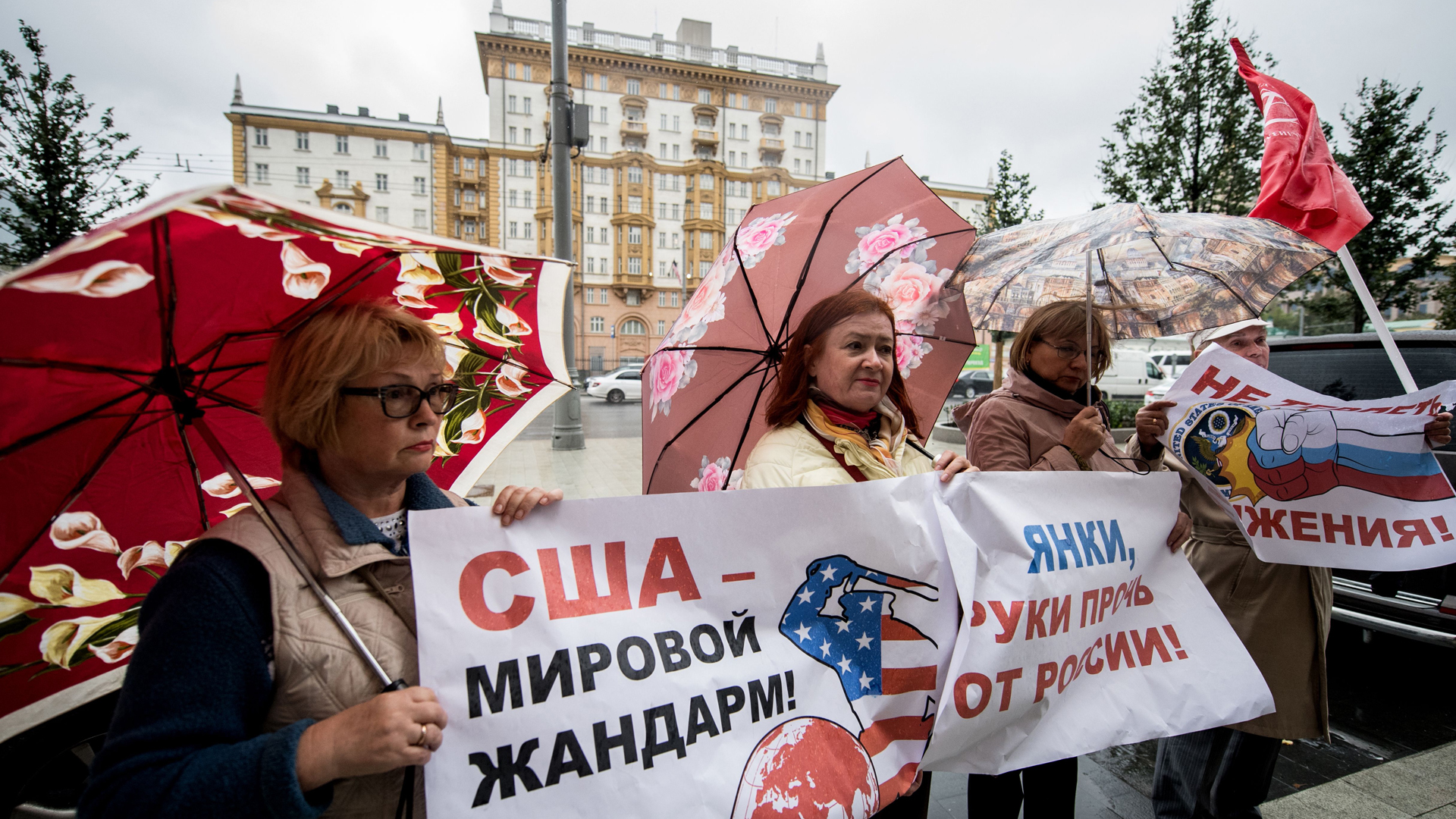"""Russian communist party supporters hold a poster reading """"USA is a policeman of the world"""" during a rally in Moscow Sept. 5, 2017, against the U.S.'s closure of Russian diplomatic offices. (Credit: Yuri Kadobnov/AFP/Getty Images)"""