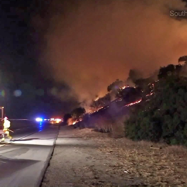 Firefighters battle a blaze near the 57 Freeway in Diamond Bar on Oct. 18, 2017. (Credit: Southern Counties News)