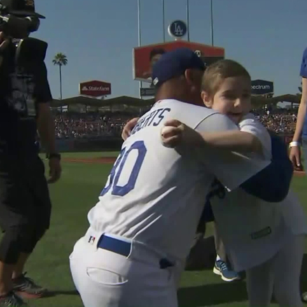 Elysa Shapiro hugs Dodgers manager Dave Roberts after throwing out the first pitch at Dodger Stadium on July 30, 2017. (Courtesy: Cedars-Sinai)