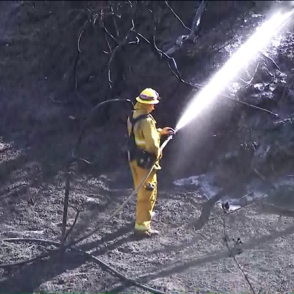 A firefighter sprays water on a hot spot in Tustin after the Canyon Fire swept through the Cowan Heights area. (Credit: KTLA)