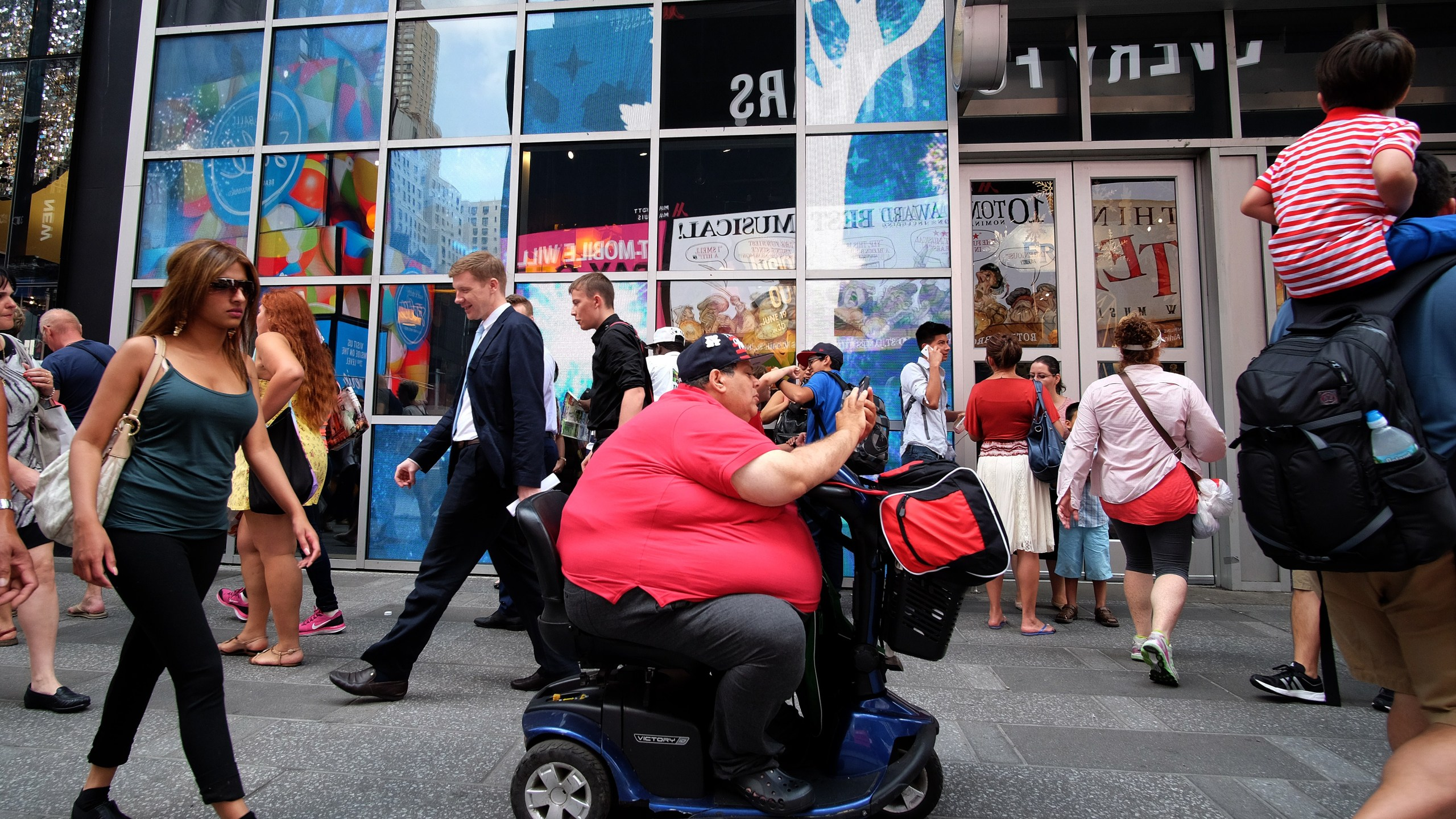 A man on an electric scooter makes his way with other pedestrians in New York on July 1, 2015. (Credit: Jewel Samad / AFP / Getty Images)