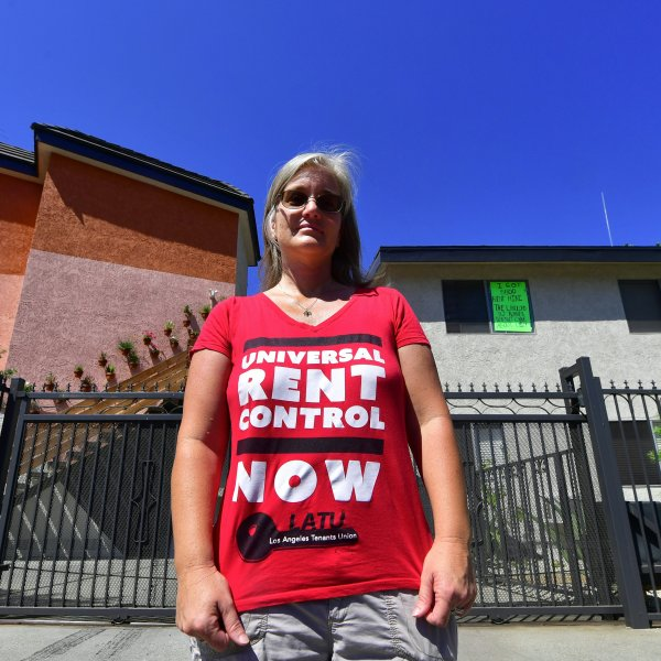 Community activist Elizabeth Blaney stands in front of the apartment block where, with no rent control due to the year it was built, the landlord has increased some rentals by as much as $800, Aug. 3, 2017, in the Boyle Heights. (Credit: FREDERIC J. BROWN/AFP/Getty Images)