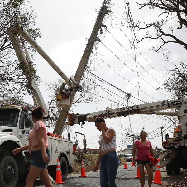 An electrical crew attempts to repair power lines that were knocked over Hurricane Maria passed through on Sept. 27, 2017, in Corozal, Puerto Rico. (Credit: Joe Raedle/Getty Images)