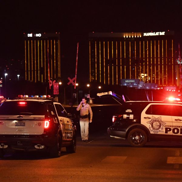 Police form a perimeter around the road leading to the Mandalay Hotel (background) after a gunman killed at least 50 people and wounded more than 200 others when he opened fire on a country music concert in Las Vegas on Oct. 2, 2017. (Credit: MARK RALSTON/AFP/Getty Images)