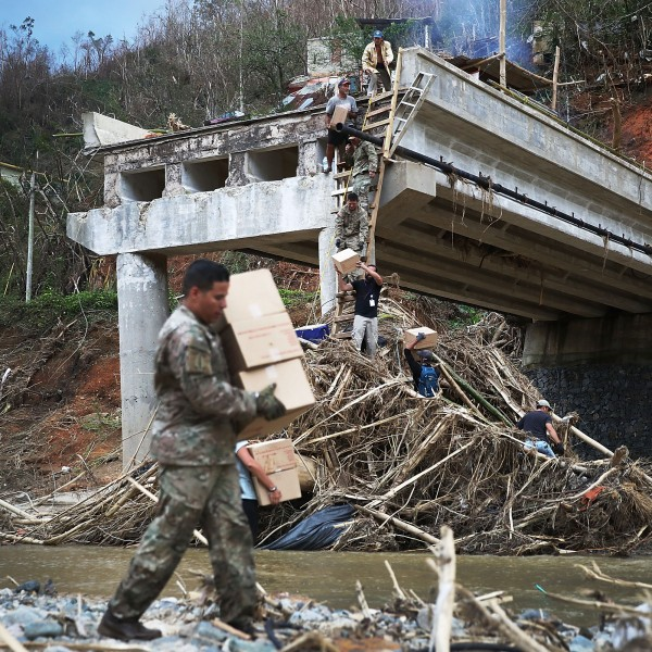 Members of the U.S. Army deliver boxes up a makeshift ladder to people that were cut off after a bridge collapsed when Hurricane Maria swept through Puerto Rico, Oct. 5, 2017, in the town of Utuado. (Credit: Joe Raedle / Getty Images)
