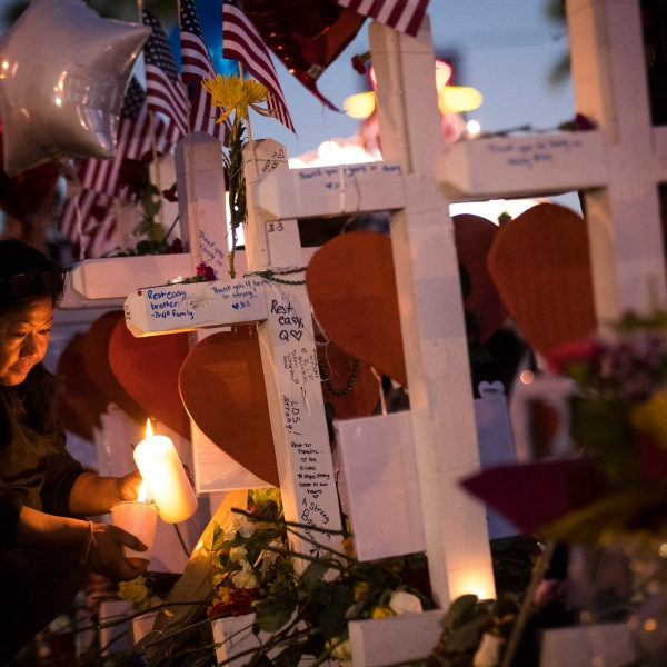 A woman lights candles at several of the 58 white crosses at a makeshift memorial on the south end of the Las Vegas Strip, Oct. 6, 2017 in Las Vegas, Nevada. (Credit: Drew Angerer / Getty Images)
