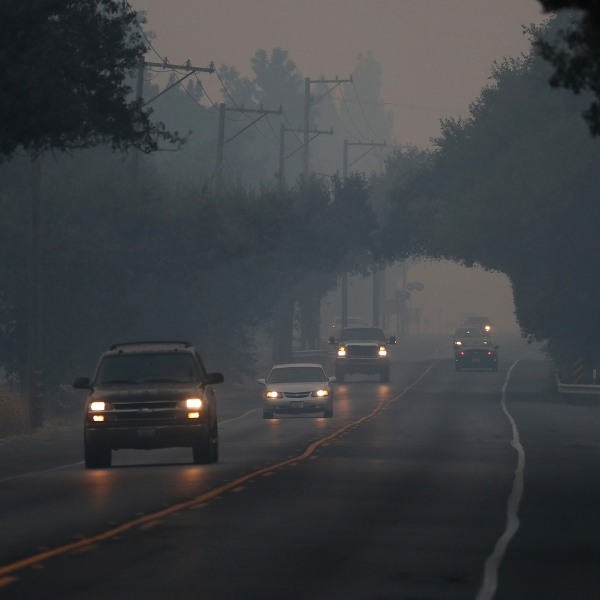 Cars drive through thick smoke along Route 29 on Oct. 13, 2017, in Yountville, California. (Credit: Justin Sullivan / Getty Images)