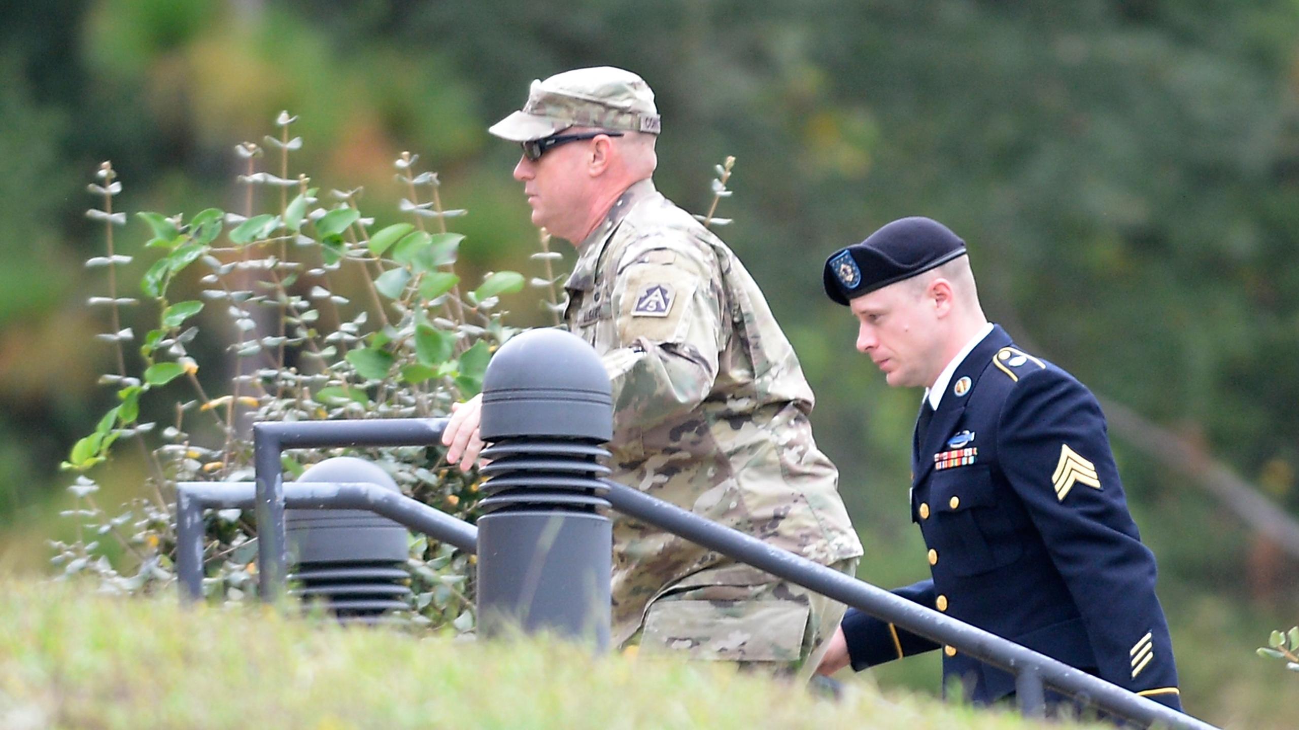 "U.S. Army Sgt. Robert Bowdrie ""Bowe"" Bergdahl (right) is escorted into the Ft. Bragg military courthouse for a motions hearing on October 16, 2017 in Fort Bragg, North Carolina. Bergdahl faces charges of desertion and endangering troops stemming from his decision to leave his outpost in 2009, which landed him five years in Taliban captivity. (Credit: Sara D. Davis/Getty Images)"