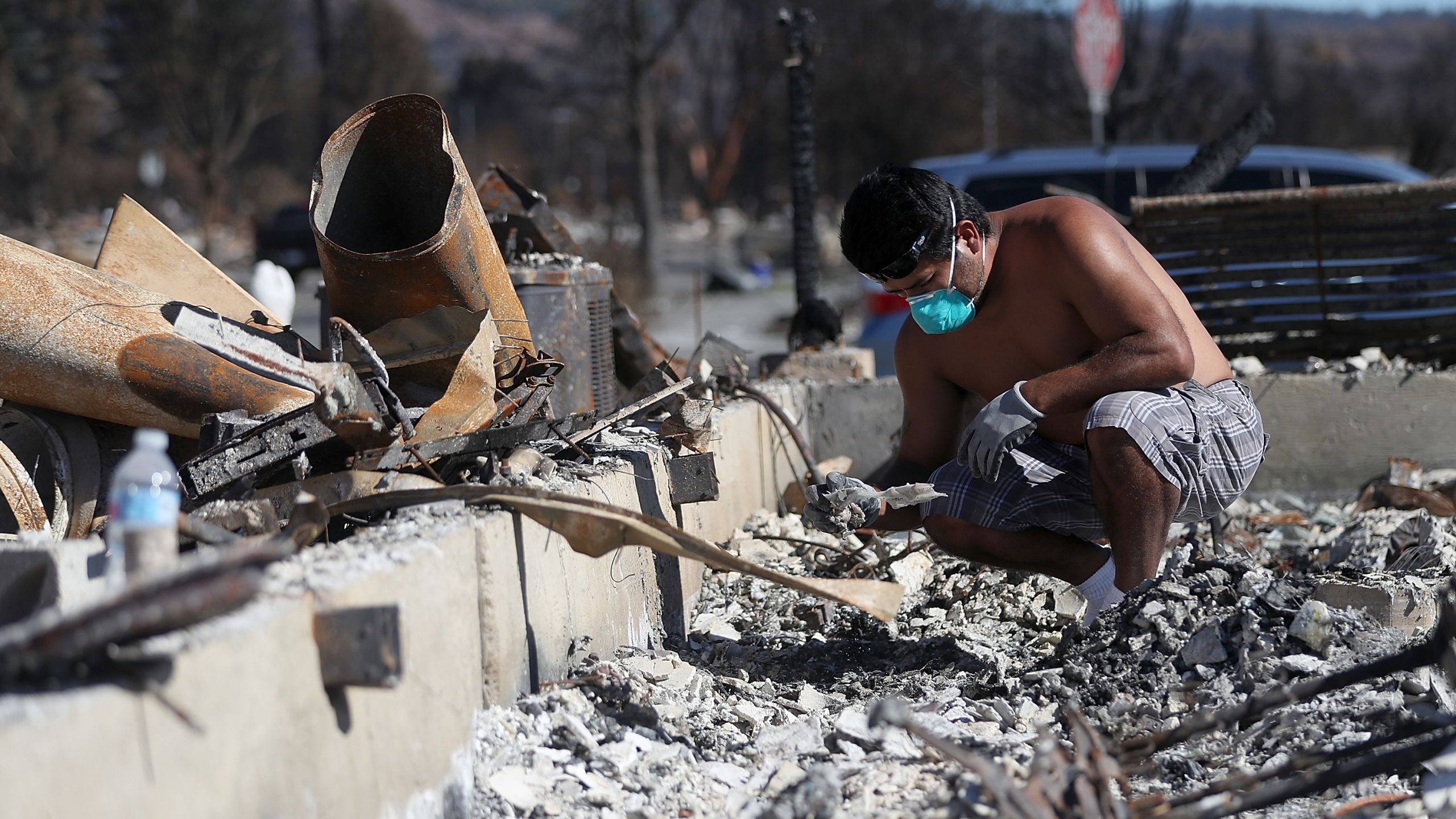 Ben Hernandez sifts through the remains of his Coffey Park home that was destroyed by the Tubbs Fire on Oct. 23, 2017, in Santa Rosa. (Credit: Justin Sullivan / Getty Images)