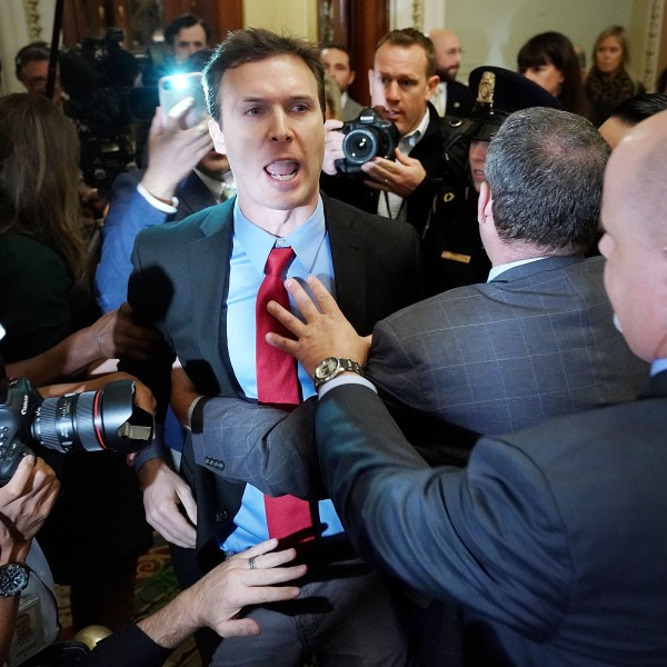 Ryan Clayton of Americans Take Action (center) is corralled by police after he threw paper Russian flags at Senate Majority Leader Mitch McConnell (R-KY) and Donald Trump as they arrived for the Republican Senate Policy Luncheon at the U.S. Capitol October 24, 2017 in Washington, DC. (Credit: Chip Somodevilla/Getty Images)