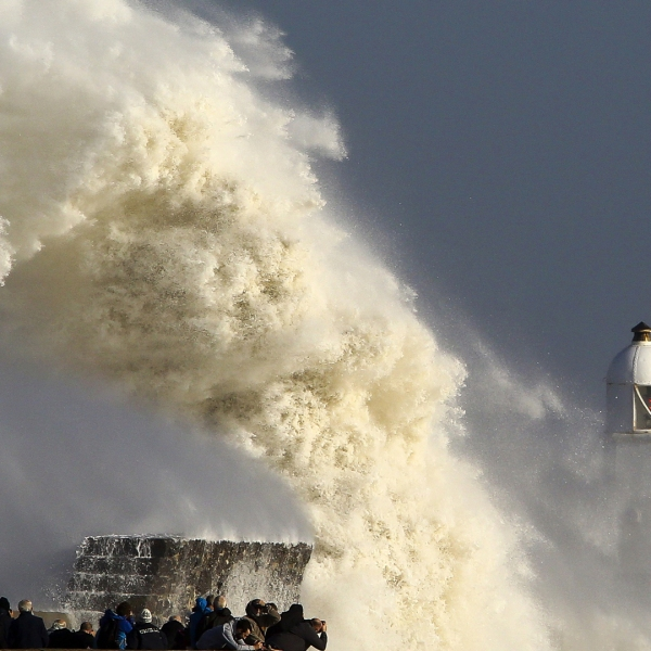 Huge waves smash against the harbor wall and lighthouse at Porthcawl, south Wales, on Oct. 16, 2017, as Hurricane Ophelia hits the UK and Ireland. (Credit: Geoff Caddick/AFP/Getty Images)
