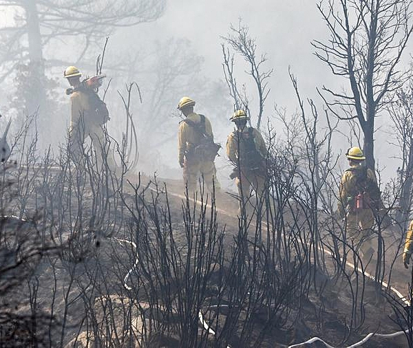 Firefighters cut a path through charred terrain as they work Oct. 17, 2017, to extinguish a fire that scorched the area near Mount Wilson. (Credit: Irfan Khan / Los Angeles Times)