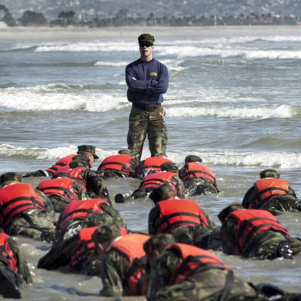 A Navy SEAL instructor assists students during an exercise on April 15, 2003, in Coronado, Calif. Credit: Photographer's Mate 2nd Class Eric S. Logsdon/U.S. Navy via Getty Images)