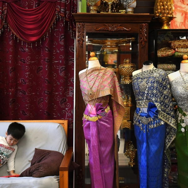 A boy sits near traditional Cambodian clothing at a shop in Long Beach's Cambodia Town. (Credit: Christina House/ Los Angeles Times)