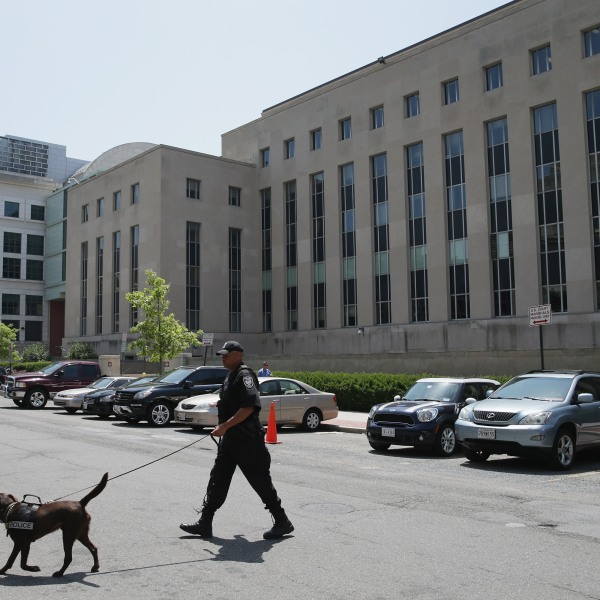 A Federal Facilities Protection Service K-9 and handler inspect the vehicles parked outside Prettyman Federal Court House where Ahmed Abu Khattala, one of the suspected ringleaders of the 2012 attacks in Benghazi, Libya, had a pretrial detention hearing July 2, 2014 in Washington, D.C. (Credit: Chip Somodevilla/Getty Images)