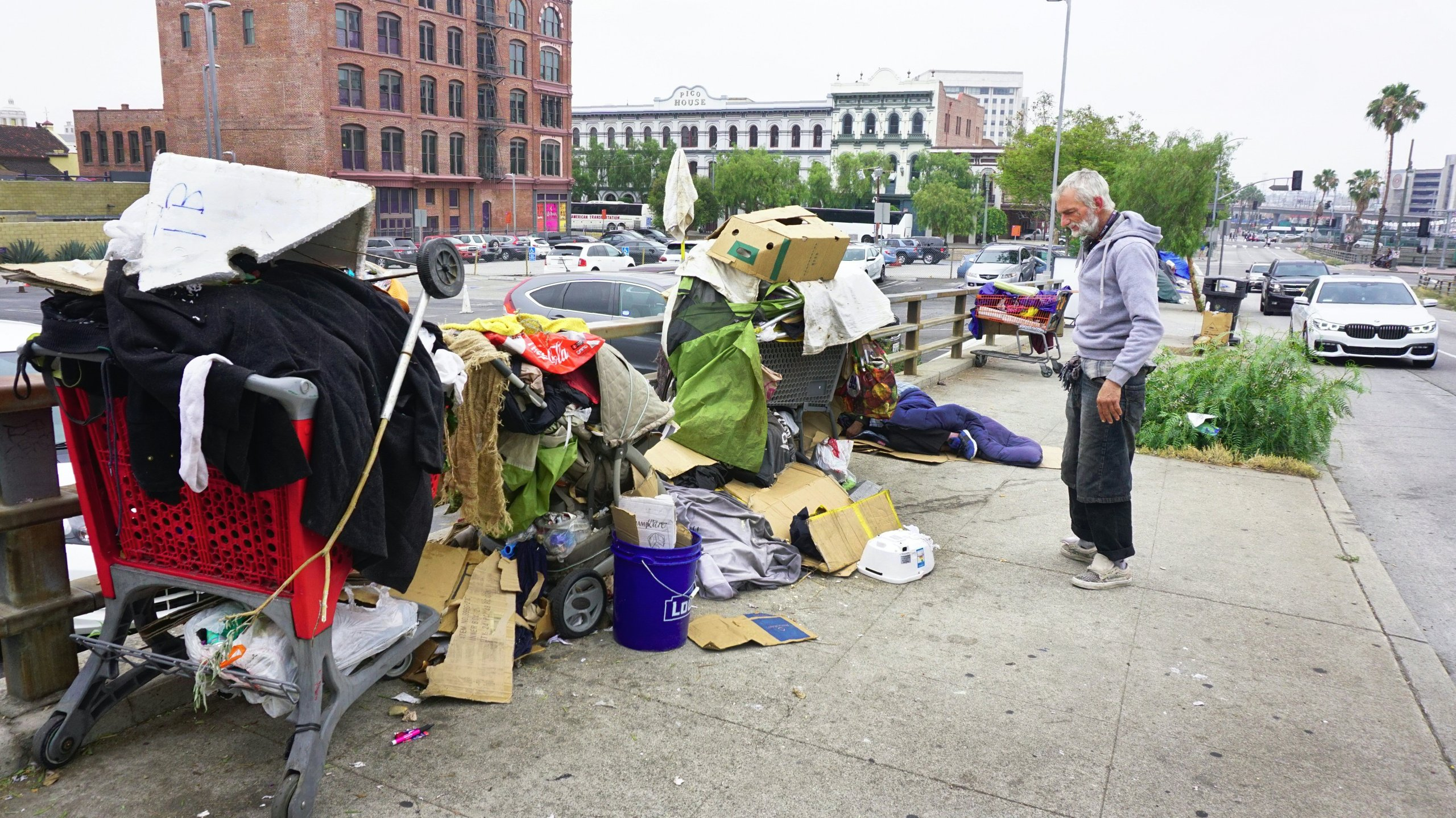 A homeless man stands before his belongings at his encampment on a downtown Los Angeles sidewalk as vehicles pass by on June 7, 2017. (Credit: Frederic J. Brown / AFP / Getty Images)