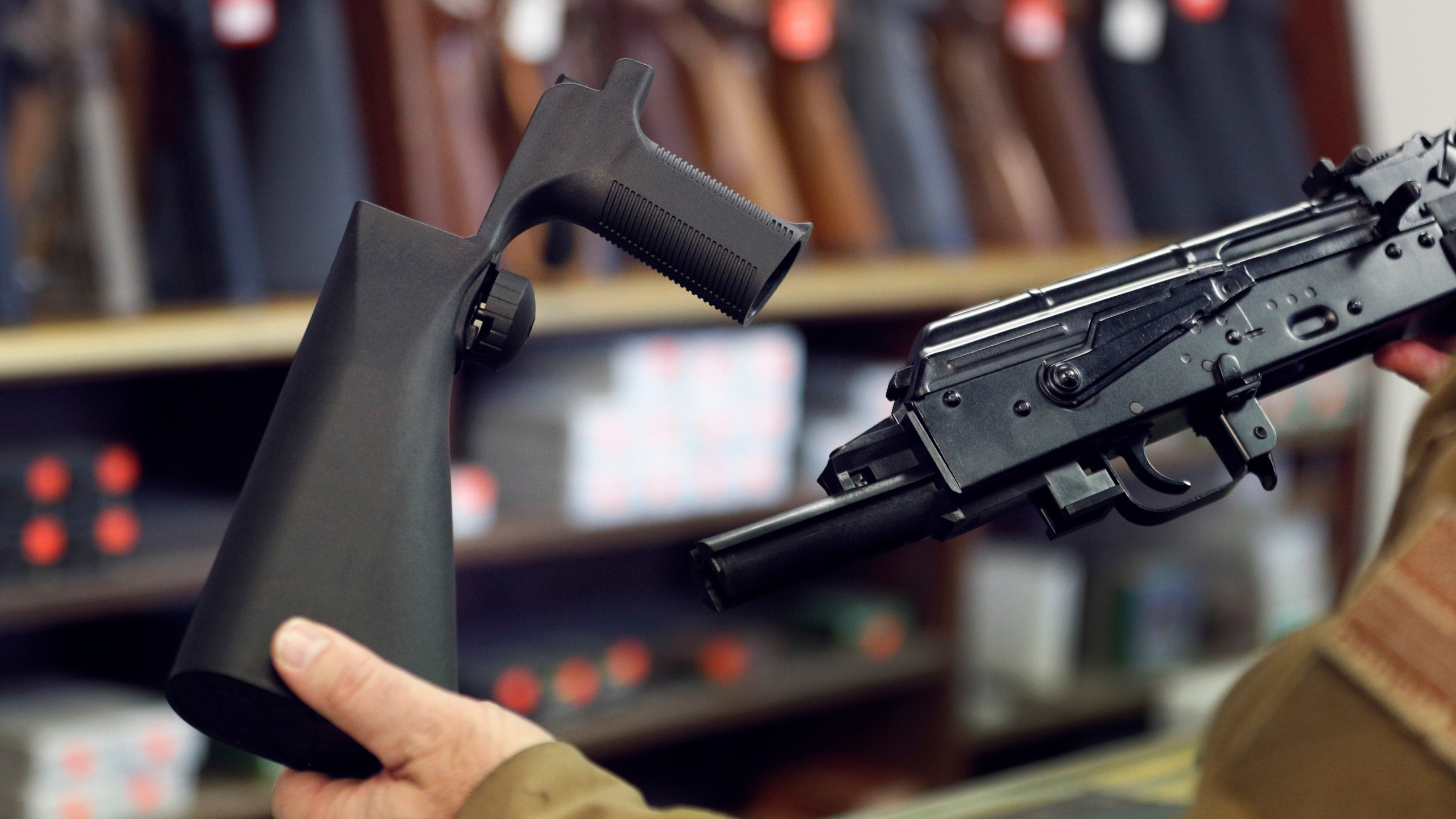A bump stock device (left), is shown next to a AK-47 semi-automatic rifle (right). (Credit: George Frey/Getty Images)