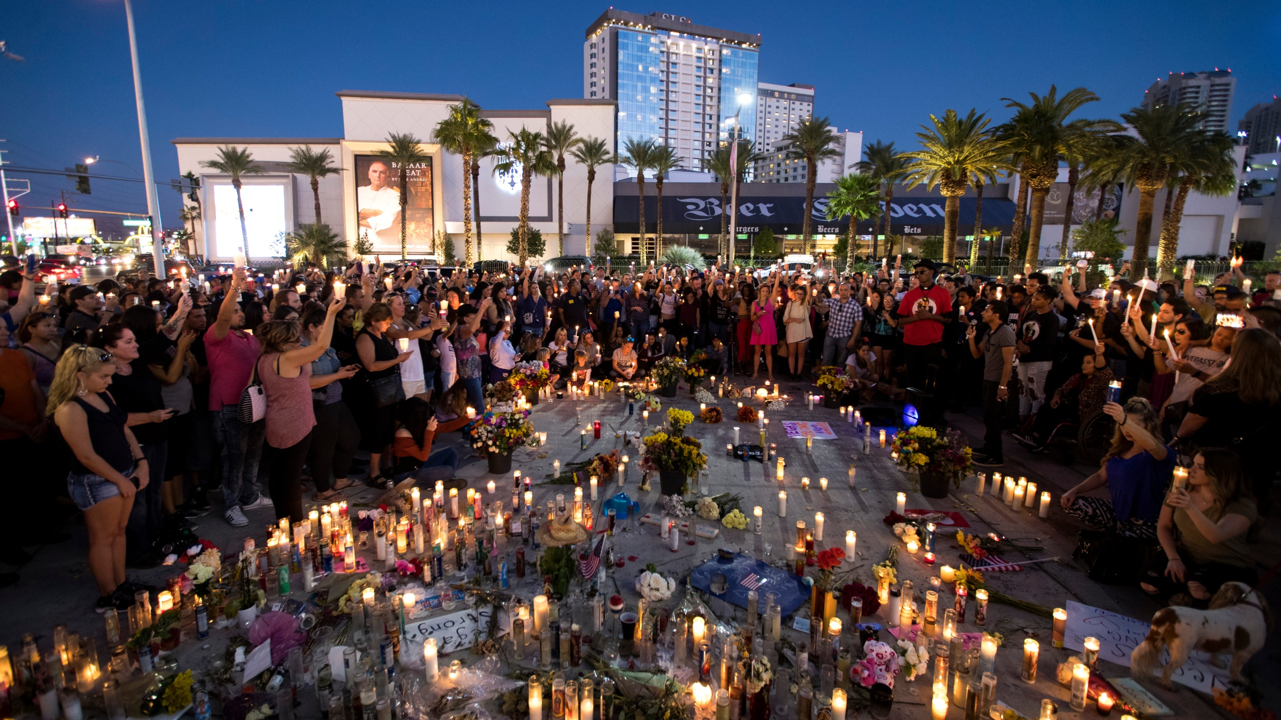 Mourners hold their candles in the air for a moment of silence during a vigil on the Las Vegas Strip to mark one week since the mass shooting at the Route 91 Harvest country music festival, Oct. 8, 2017. (Credit: Drew Angerer / Getty Images)