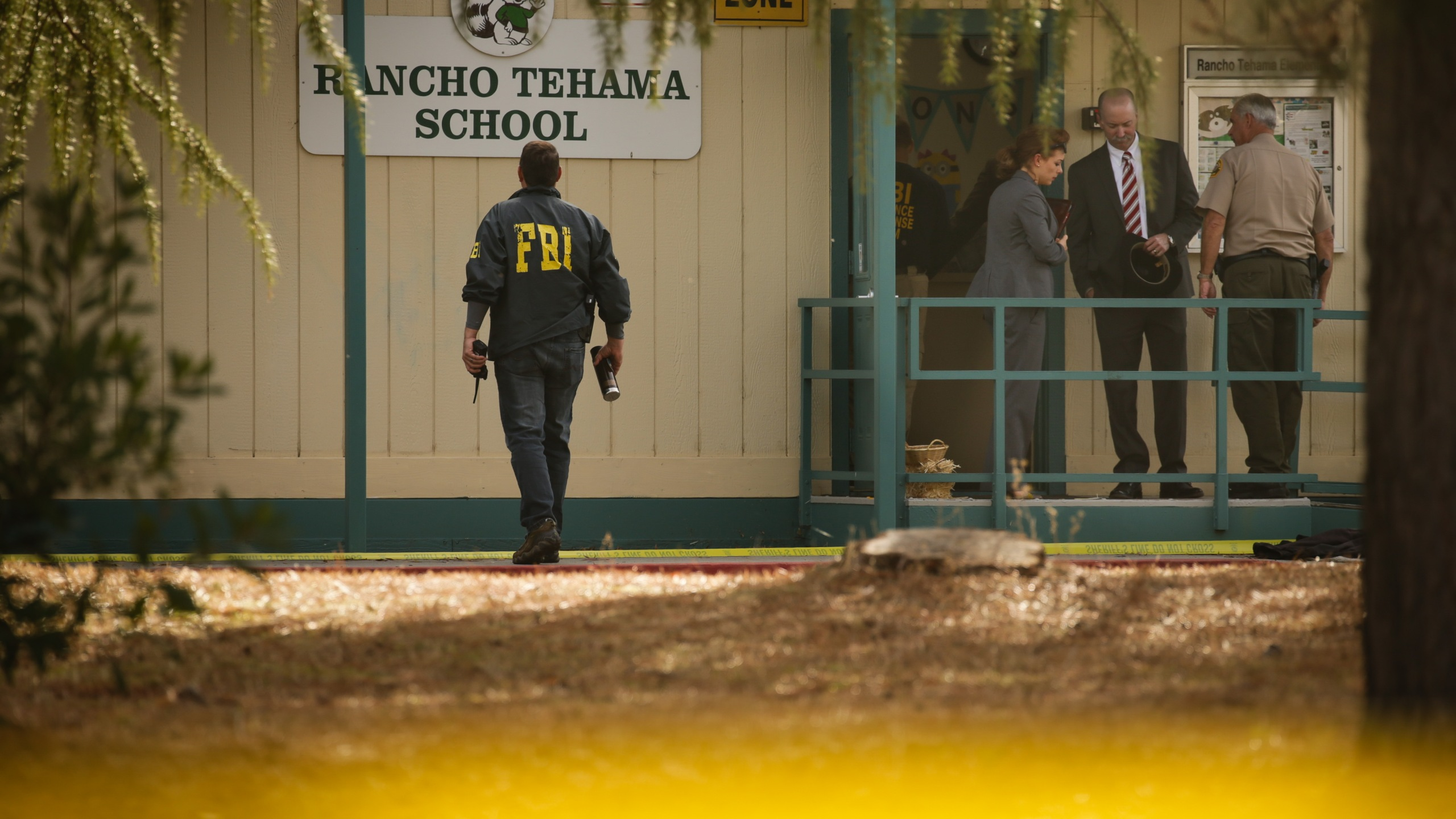 FBI agents are seen behind yellow crime scene tape outside Rancho Tehama Elementary School after a shooting in the morning on November 14, 2017, in Rancho Tehama, California. Witness Brian Rogers – who was across the street when the first shots rang out – said he heard single-fire shots by the school as if someone were taking time to pick targets a shot and the yelp of a dog, and to the south, a man at the municipal airport screaming for help, and more shooting there. (Credit: ELIJAH NOUVELAGE/AFP/Getty Images)