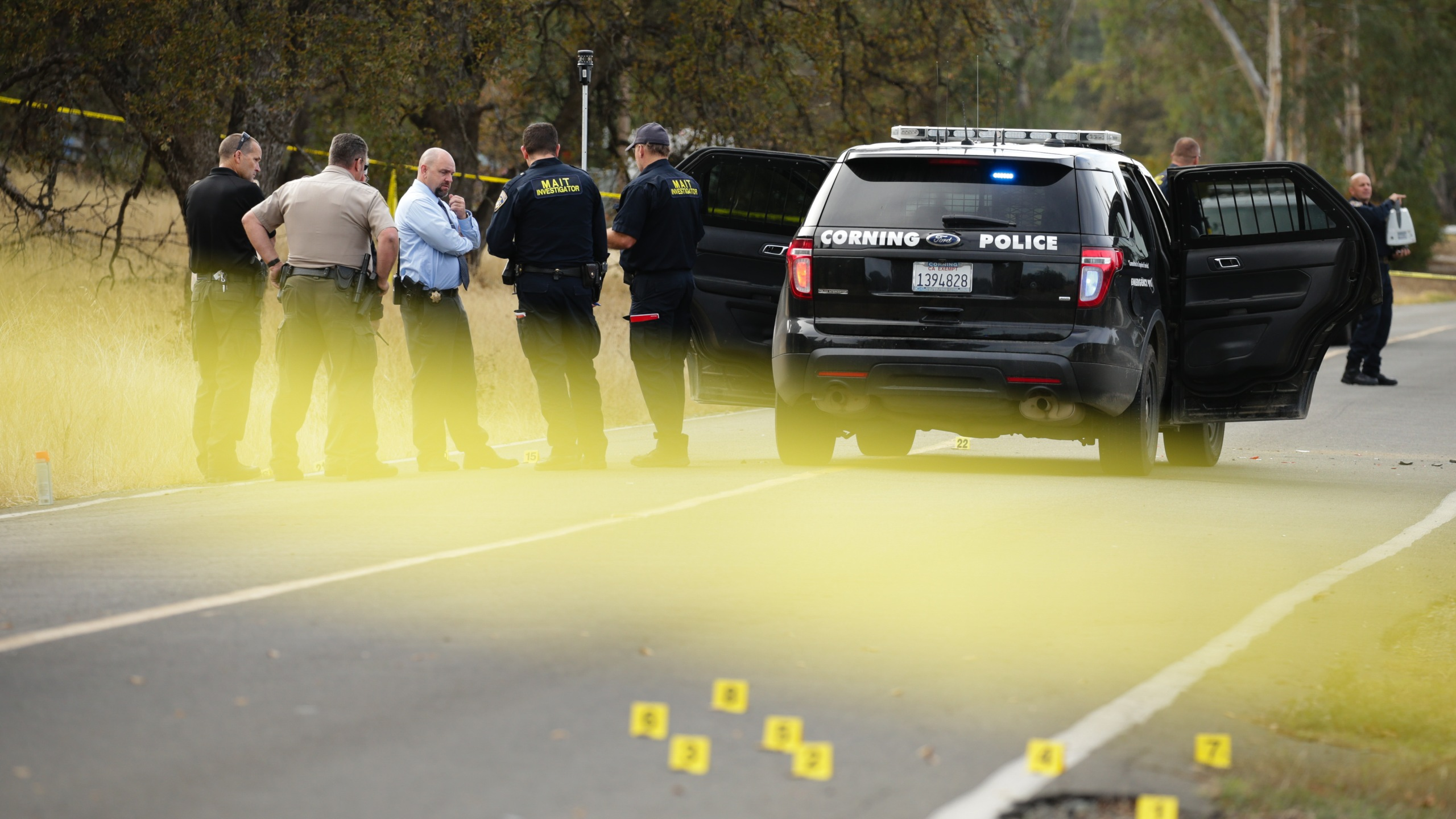 Law enforcement officers and investigators converse near a police vehicle that was involved in a shooting on November 14, 2017, in Rancho Tehama, California. (Credit: Elijah Nouvelage/AFP/Getty Images)