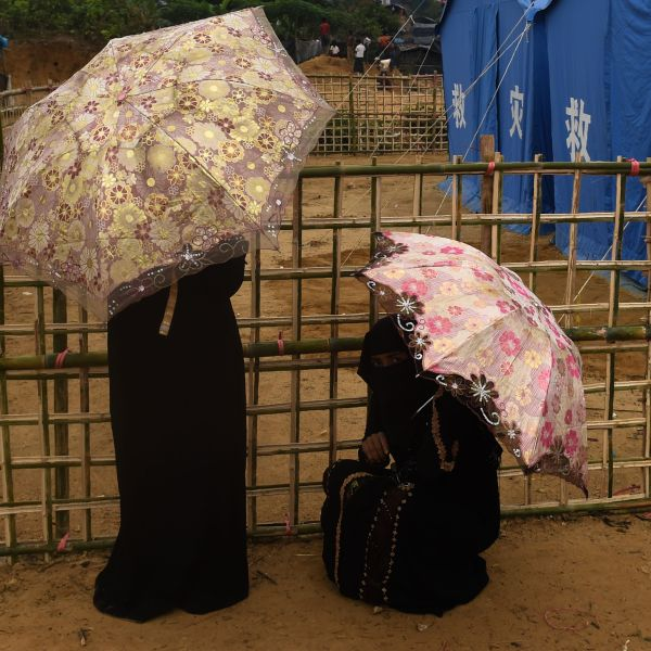 Rohingya refugee women rest with umbrella during a drizzle at Thankhali refugee camp in the Bangladeshi district of Ukhia on Nov. 17, 2017. (Credit: Munir Uz Zaman / AFP / Getty Images)