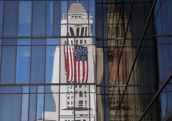 The American flag draped on Los Angeles City Hall is reflected in the windows of LAPD headquarters in September. (Credit: Al Seib / Los Angeles Times)