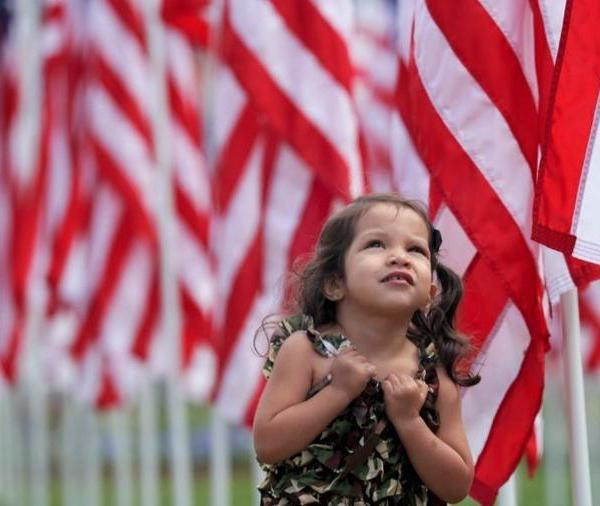 Mariana Quezada-DeAnda, 2, plays among hundreds of flags installed on the front lawn of Azusa City Hall to honor veterans and service persons. (Credit: Irfan Khan / Los Angeles Times)