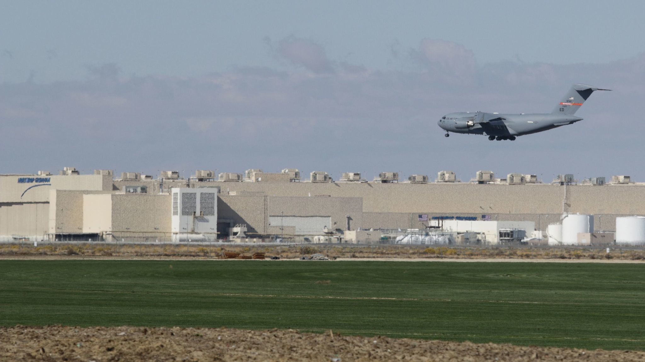 A Boeing C-17 Globemaster III lands at Palmdale Regional Airport during recent exercise flights. Northrop Grumman (background) was awarded the new B-21 bomber contract in 2015. (Credit: Myung J. Chun / Los Angeles Times