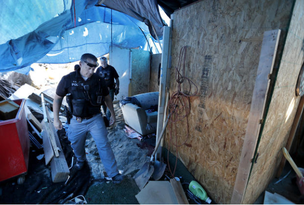 Officers from the Orange County Sheriff's Department and the Anaheim, Orange and Fountain Valley police departments have been clearing out homeless camps along the Santa Ana River trail in November 2017. (Credit: Allen J. Schaben / Los Angeles Times)