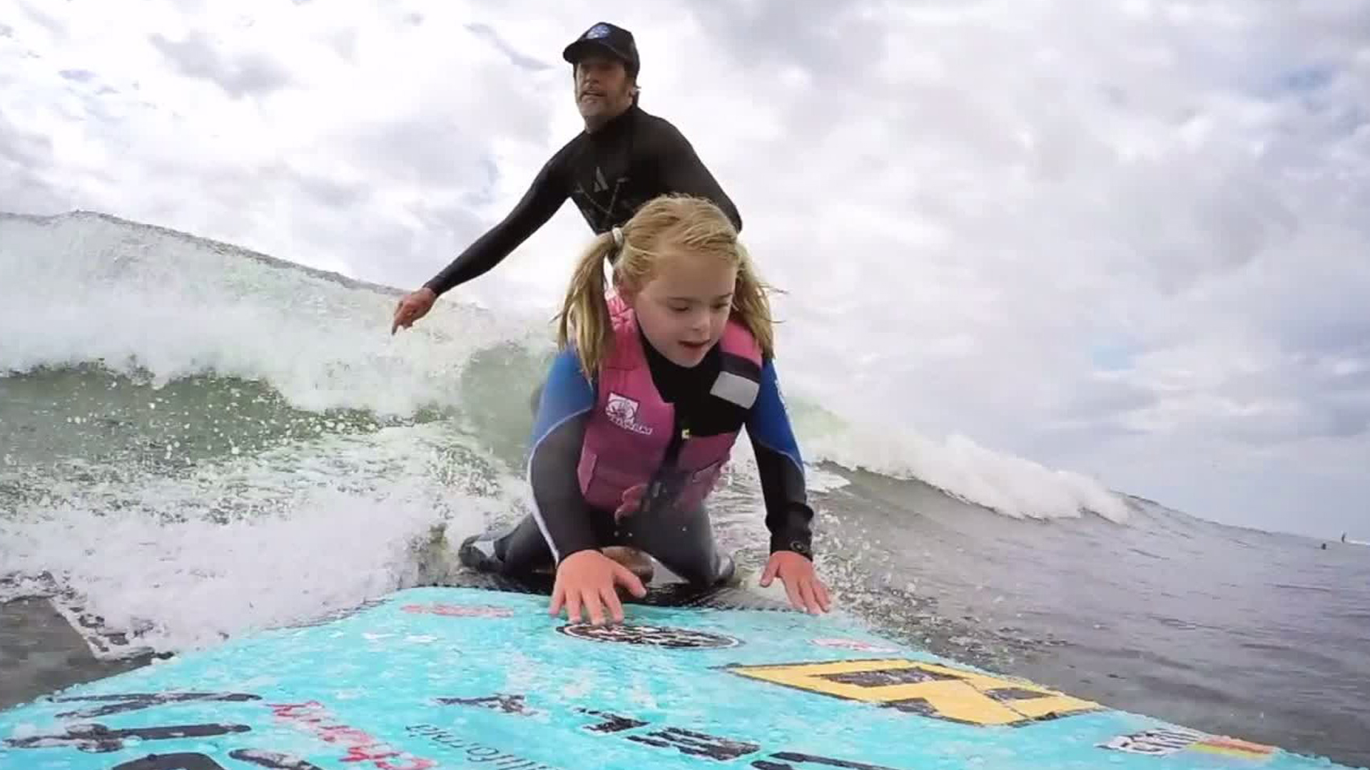 """A surfer catches a wave while a young girl rides the tip of his board during a """"A Walk on Water"""" event in Malibu on November 11, 2017. (Credit: KTLA)"""
