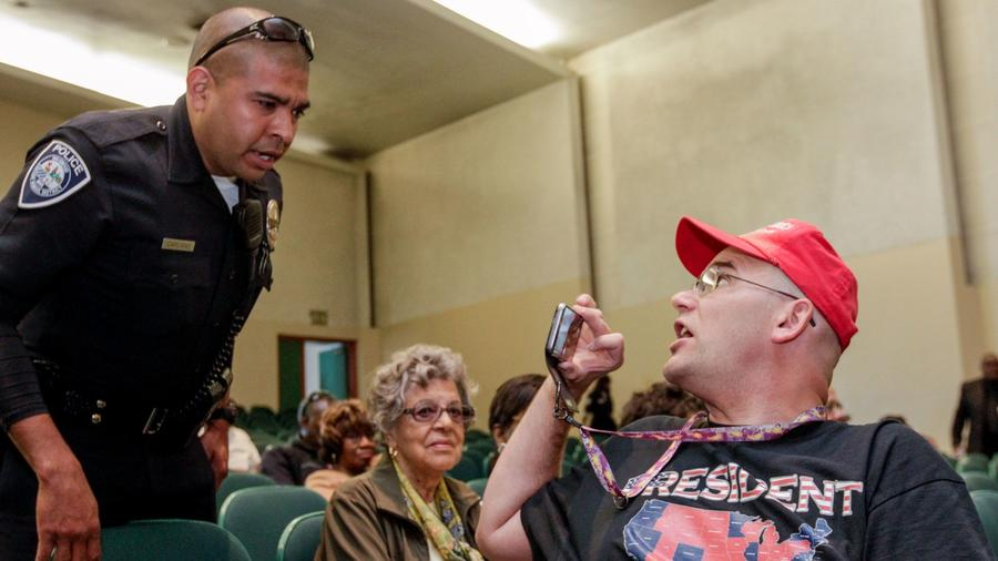 An Inglewood police officer talks to outspoken conservative activist Arthur Schaper at a town hall meeting held by Maxine Waters in May, 2017. (Credit: Irfan Khan / Los Angeles Times)