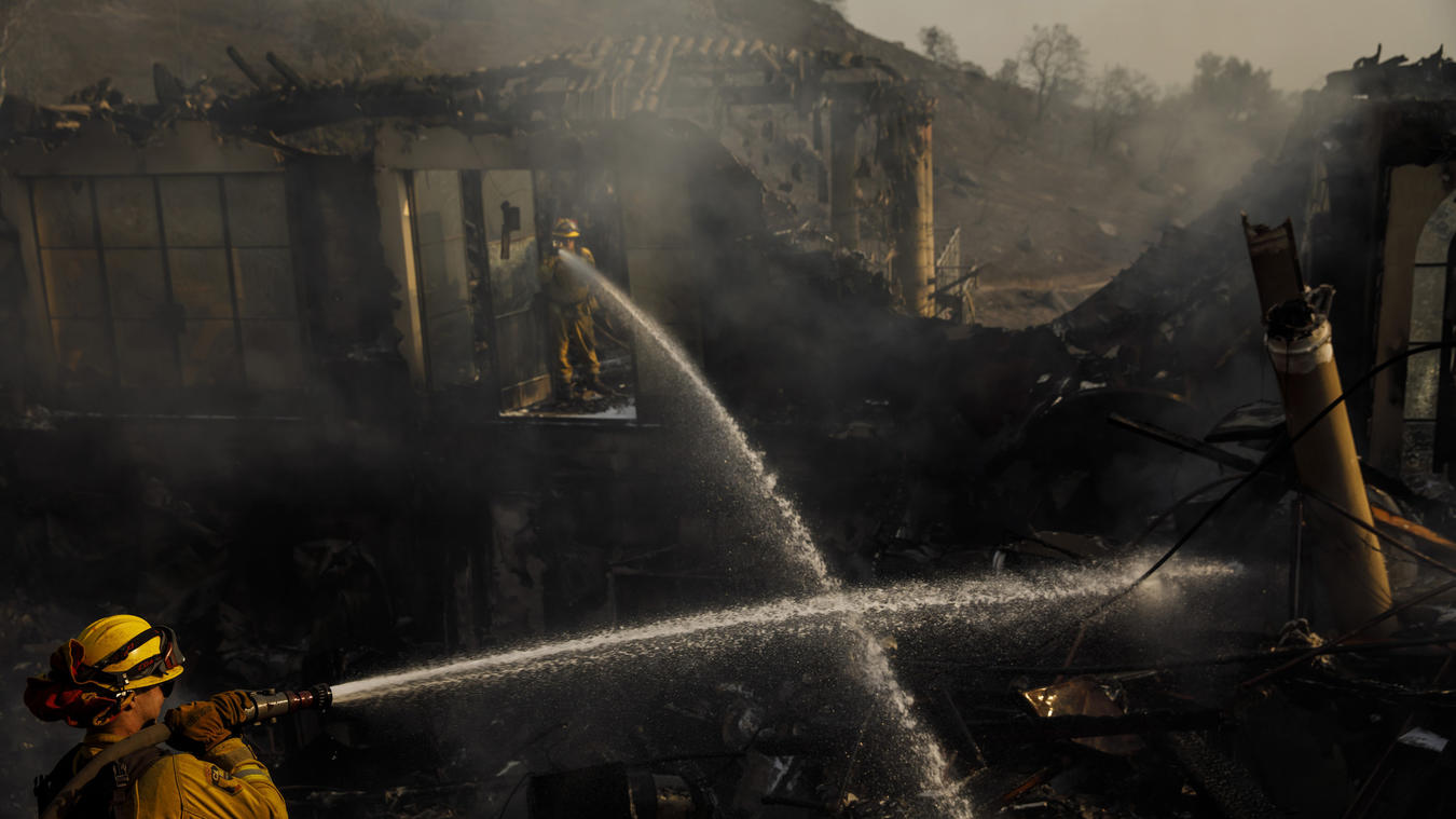 Humboldt County firefighters Lonnie Risling, left, and Jimmy McHaffie, right, spray down smoldering fire underneath the rubble of a home that was destroyed by the Thomas Fire, in Montecito on Dec. 17, 2017. (Credit: Marcus Yam/ Los Angeles)