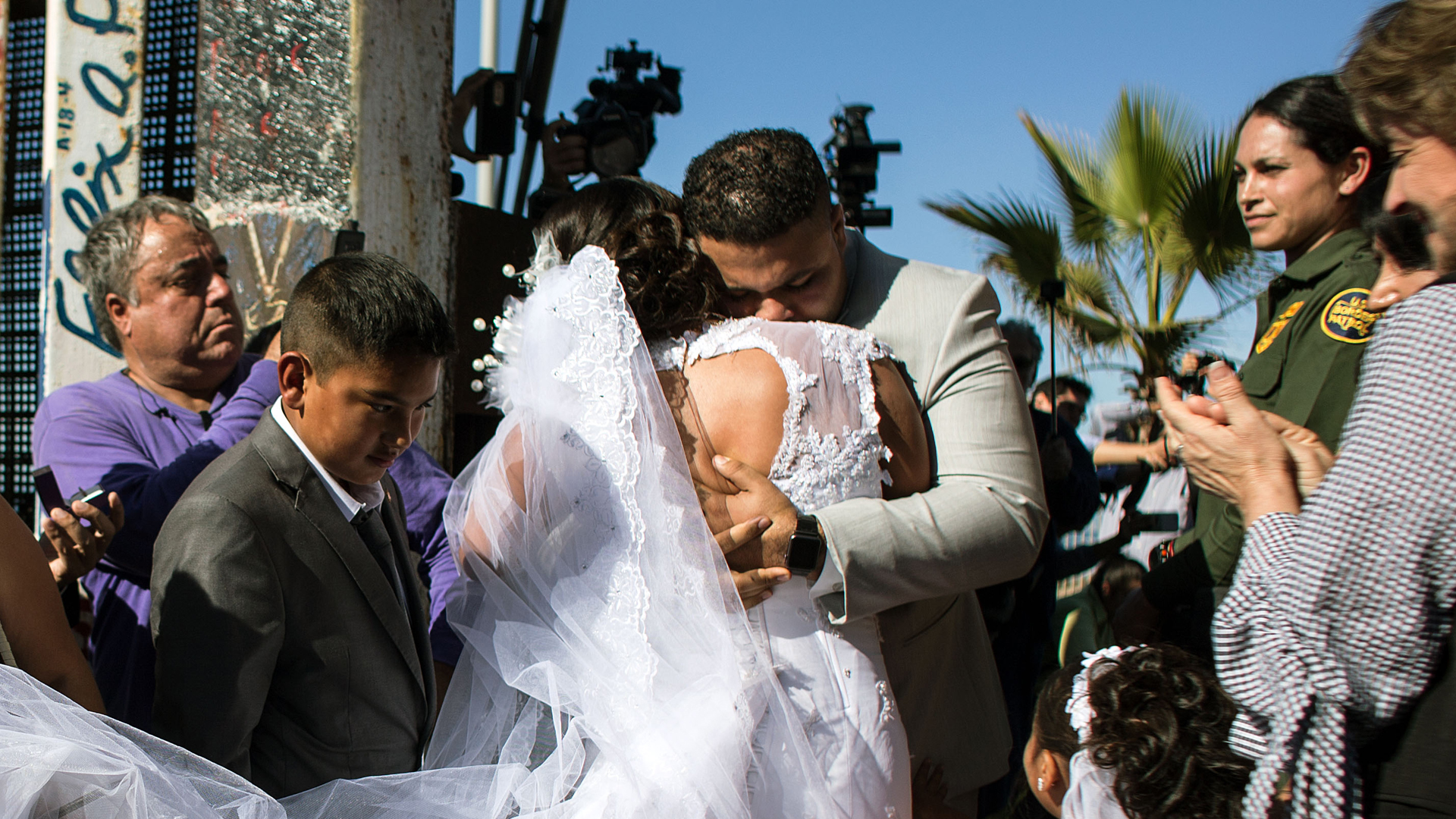 Brian Houston is seen hugging the bride at his wedding on the U.S.-Mexico border on Nov. 18, 2017. (Credit: GUILLERMO ARIAS/AFP/Getty Images)