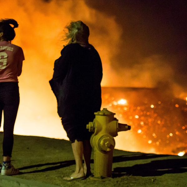 Residents watch as the Creek Fire burns along a hillside near homes in the Shadow Hills neighborhood of Los Angeles on Dec. 5, 2017. (Credit: Kyle Grillot/AFP/Getty Images)