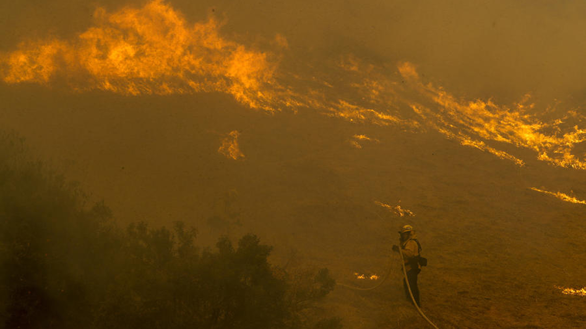 A firefighter battles flames in poor visibility in Lake View Terrace on Dec. 5, 2017. (Credit: Irfan Khan / Los Angeles Times)