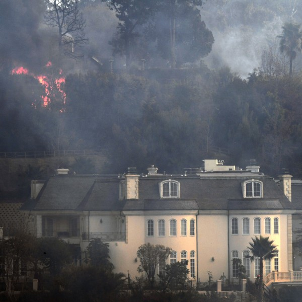 Flames are seen behind a Bel-Air mansion threatened by the Skirball Fire on Dec. 6, 2017. (Credit: AFP PHOTO / Robyn Beck)